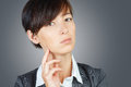 Pensive business woman portrait of young on a gray background Royalty Free Stock Photos