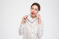 Pensive business woman talking on mobile phone and holding glasses Royalty Free Stock Photo