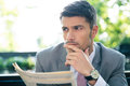 Pensive businessman holding newspaper Royalty Free Stock Photo