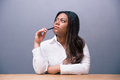 Pensive businesswoman sitting at the table with pen african and looking up over gray background Stock Image