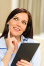Pensive cheerful woman holding digital tablet portrait of Royalty Free Stock Photo