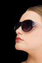 Pensive classy blonde wearing sunglasses on black background Stock Images