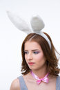 Pensive cute woman in rabbit ears looking away over gray background Stock Photos