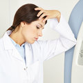 Pensive female doctor in hospital thinking a leaning on mri machine Royalty Free Stock Photos