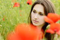 Pensive girl in poppies field brunette Royalty Free Stock Photo