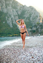 Pensive girl walking on summer sea beach in bikini Royalty Free Stock Photo