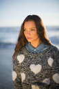 Pensive gorgeous woman with pullover posing on the beach at dusk Royalty Free Stock Photos