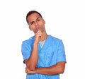 Pensive guy nurse standing with hand on chin portrait of a white background Stock Photo