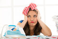 Pensive housewife daydreaming leaning on an ironing board holding her head in front of her are iron and laundry basket Royalty Free Stock Image