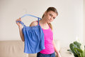 Pensive lady standing with blouse on hanger