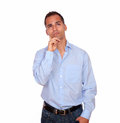 Pensive latin adult man looking up portrait of a on blue shirt on isolated background copyspace Stock Photography
