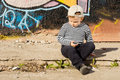 Pensive little boy sitting thinking as he sits on the pavement in front of a wall painted in colourful graffiti in the sunshine Stock Image