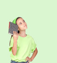 Pensive little girl with headband and a book isolated on green background Stock Photography