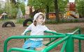 Pensive little girl rides on small carousel Royalty Free Stock Photography