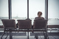 Pensive lonely woman tourist in airport terminal sitting on chair and looking on airplanes through window in departure holding zon Royalty Free Stock Photo