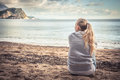 Pensive lonely young woman sitting on beach hugging her knees and looking into the distance with hope Royalty Free Stock Photo