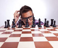 Pensive man in front of his first chess move Royalty Free Stock Photos