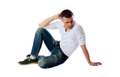 Pensive man sitting at the floor over white background Stock Image