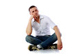 Pensive man sitting at the floor over white background Stock Photos
