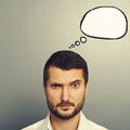 Pensive man with speech bubble empty looking at camera over grey background Royalty Free Stock Images