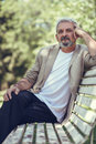 Pensive mature man sitting on bench in an urban park. Royalty Free Stock Photo