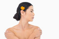 Pensive model with orange flower in hair touching her shoulders on white background Royalty Free Stock Images