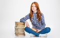 Pensive peaceful young curly female sitting near stack of books with legs crossed the over white background Royalty Free Stock Photo