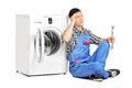 Pensive plumber fixing a washing machine isolated on white background Stock Photo