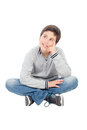 Pensive preteen boy sitting on the floor isolated a white background Stock Photo