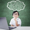Pensive student with laptop learn multi language portrait of elementary school thinking on the cloud bubble on the table Royalty Free Stock Photo