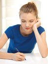 Pensive teenage girl with pen and paper picture of Royalty Free Stock Images
