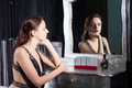 Pensive wistful young woman glamorous in evening wear sitting at her dressing table reflected in the mirror with a look of longing Stock Photo