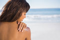 Pensive woman applying sun cream on her shoulder the beach Royalty Free Stock Image