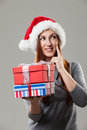 Pensive woman holding christmas gifts redhead and wearing a santa hat Stock Photography