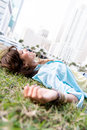 Pensive woman lying at the park on grass and looking up Stock Images