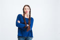 Pensive woman with two long braids standing and thinking attractive young arms crossed over white background Royalty Free Stock Photos