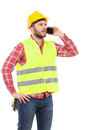 Pensive worker on the phone manual in yellow helmet and lime waistcoat talking cell three quarter length studio shot isolated Royalty Free Stock Photos