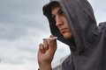 Pensive and worried teenage boy with black hoodie is smoking cig Royalty Free Stock Photo