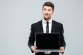 Pensive young businessman holding blank screen laptop and thinking Royalty Free Stock Photo