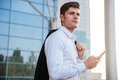 Pensive young businessman holding mobile phone with jacket over shoulder Royalty Free Stock Photo
