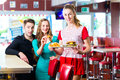 People in american diner or restaurant and waitress friends couple eating fast food fast food the wearing a short costume Stock Photography