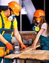 People in builder helmet man and woman with electric planer Royalty Free Stock Photos