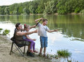 People camping and fishing, family active in nature, fish caught on bait, river and forest, summer season Royalty Free Stock Photo