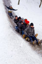 People Children ride on the winter snow sledding from hills. Winter playing, fun, snow Royalty Free Stock Photo