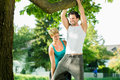 People in city park doing chins or pull ups on tree young women and personal trainer exercising under summer trees for sport Stock Images