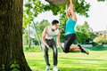 People in city park doing chins or pull ups on tree young women and personal trainer exercising under summer trees for sport Royalty Free Stock Image