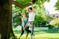 People in city park doing chins or pull ups on tree young women and personal trainer exercising under summer trees for sport Stock Photo