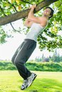 People in city park doing chins or pull ups young man exercising under summer trees for sport fitness Stock Photography