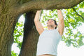 People in city park doing chins or pull ups young man exercising under summer trees for sport fitness Stock Photo