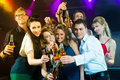 People in club or bar drinking beer young out of a bottle and have fun Stock Photo